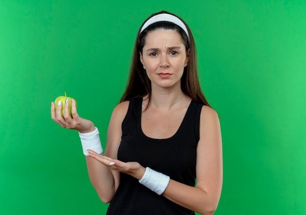 Jonge fitness vrouw die in hoofdband groene appel houdt die camera bekijkt verward status over groene achtergrond