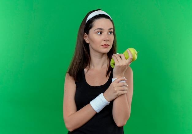 Jonge fitness vrouw die in hoofdband groene appels houdt die opzij met ernstig gezicht kijken die zich over groene achtergrond bevinden