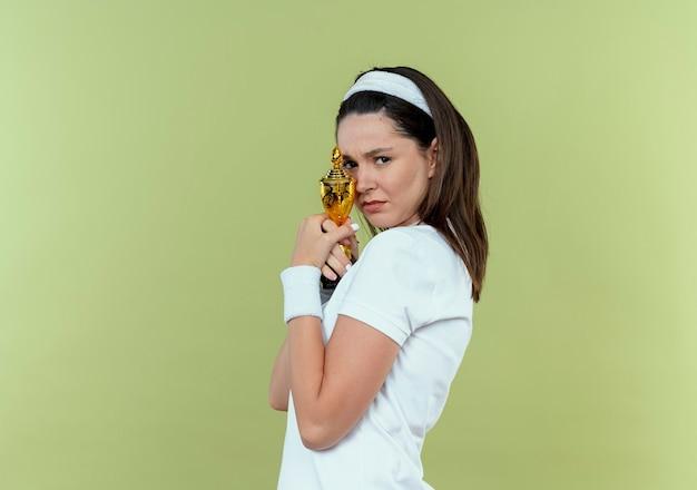 Jonge fitness vrouw die in hoofdband haar trofee met droevige uitdrukking houdt die zich over lichte muur bevindt