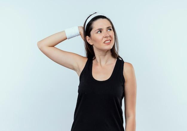 Jonge fitness vrouw die in hoofdband opzij met hand op hoofd voor fout kijkt die zich over witte achtergrond bevindt