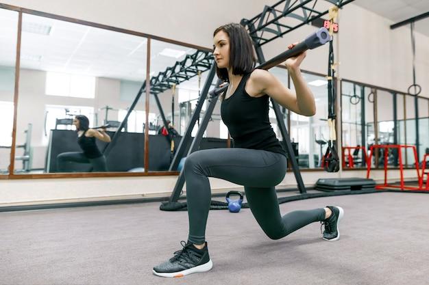 Jonge fitness vrouw die in moderne sportgymnastiek uitoefent.
