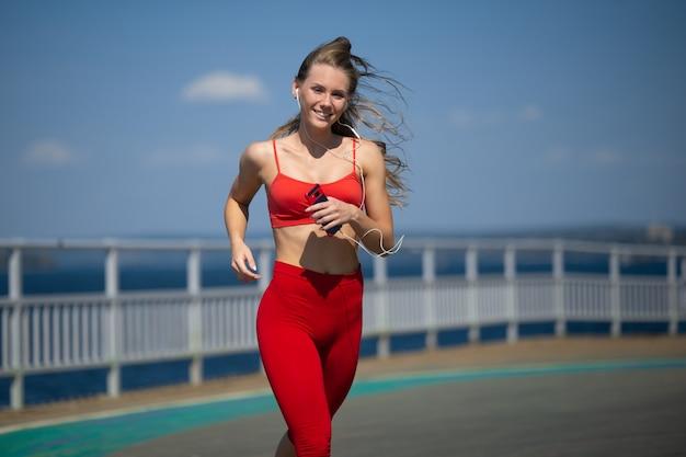 Jonge fitness vrouw die op de kust loopt. het concept van een gezonde levensstijl