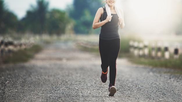 Jonge fitness vrouw die op de weg in de ochtend loopt.