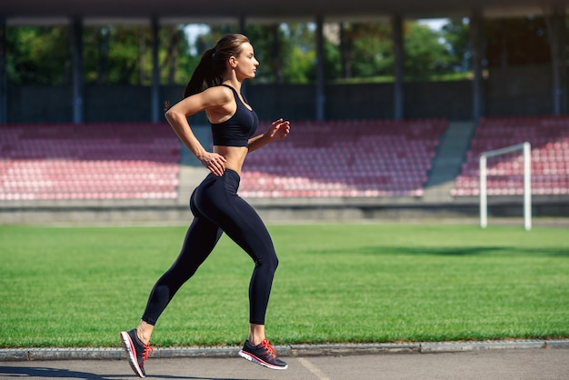 Jonge fitness vrouw die op een stadionspoor loopt