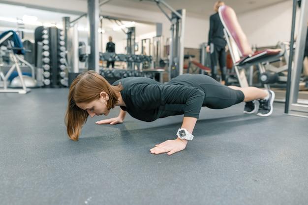 Jonge fitness vrouw die opdrukoefeningoefeningen in gymnastiek maakt