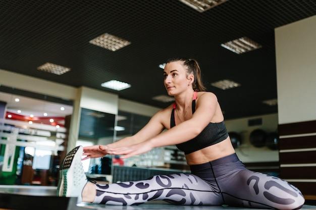 Jonge fitness vrouw doen rekoefeningen en zittend op een mat in de sportschool.