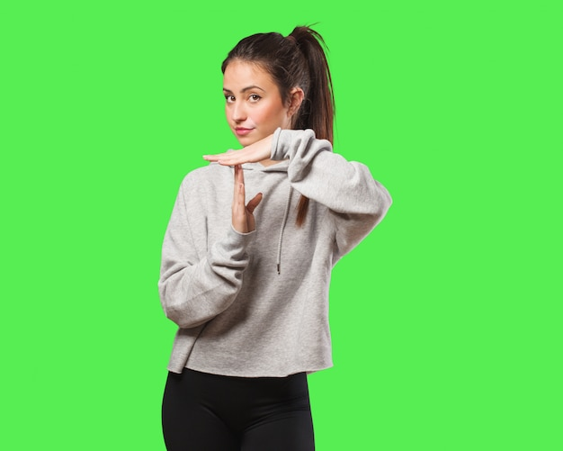 Jonge fitness vrouw doet een time-out gebaar