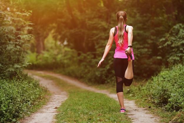 Jonge fitness vrouw doet warming-up na het joggen op het parcours in het park