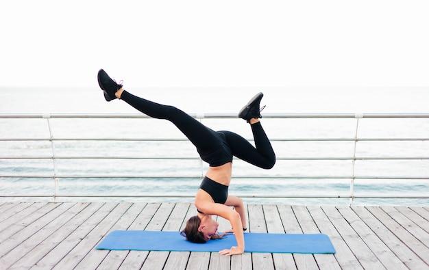 Jonge fitness vrouw doet yoga oefeningen staande op haar hoofd op een gymnastiekmat op het strand