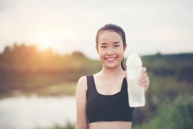 Jonge fitness vrouw hand met fles water na het uitvoeren van de oefening