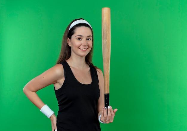 Jonge fitness vrouw in de honkbalknuppel van de hoofdbandholding die camera bekijkt die met gelukkig gezicht glimlacht dat zich over groene achtergrond bevindt