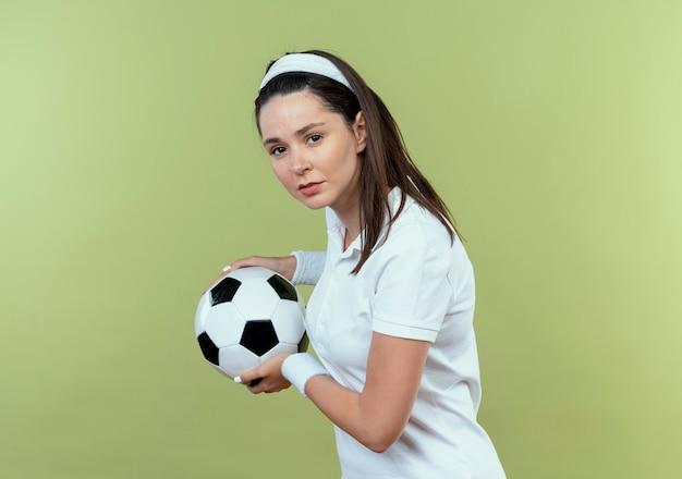 Jonge fitness vrouw in het voetbal van de hoofdbandholding met ernstig gezicht dat zich over lichte muur bevindt
