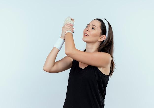 Jonge fitness vrouw in hoofdband aanraken van haar verbonden pols gevoel pijn staande op witte achtergrond