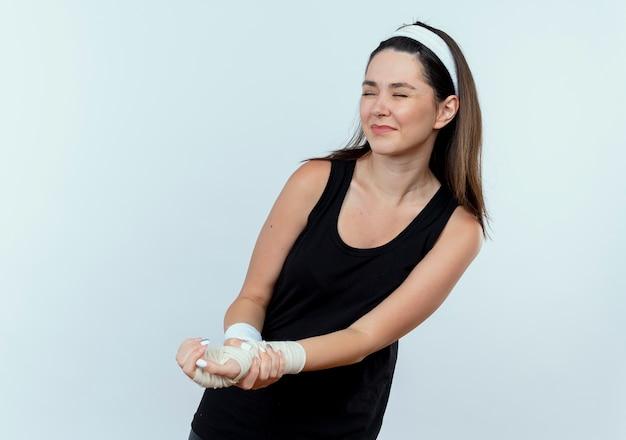 Jonge fitness vrouw in hoofdband aanraken van haar verbonden pols gevoel pijn staande over witte muur