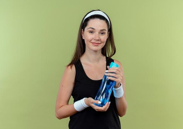 Jonge fitness vrouw in hoofdband bedrijf fles water glimlachend zelfverzekerd staande over lichte muur