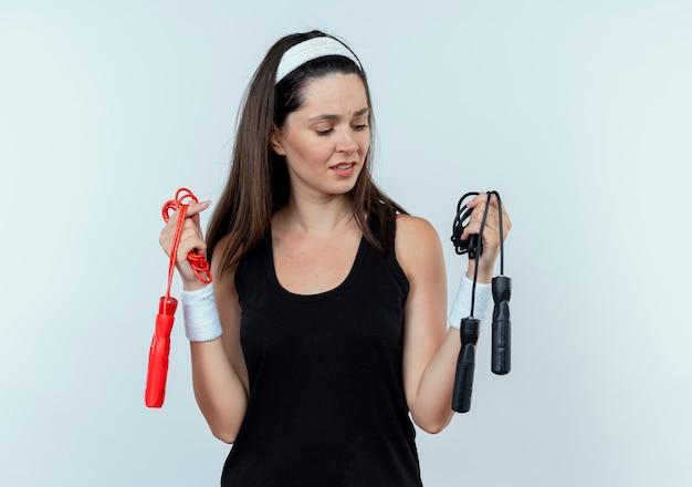 Jonge fitness vrouw in hoofdband bedrijf springtouwen op zoek verward en onzeker staande over witte muur