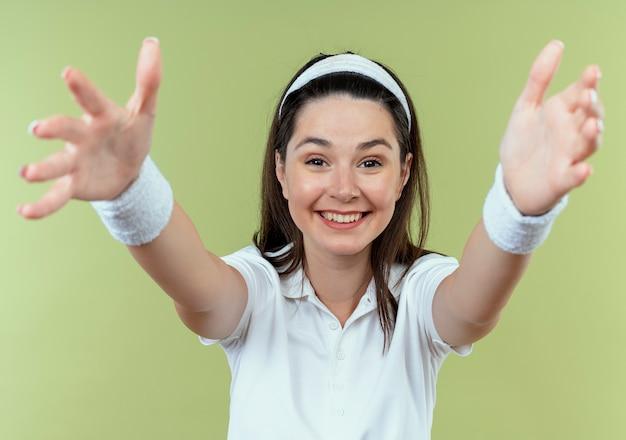 Jonge fitness vrouw in hoofdband blij en positief verwelkomend gebaar met handen permanent over lichte muur maken