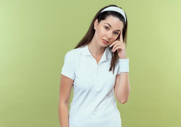 Jonge fitness vrouw in hoofdband camera kijken met peinzende uitdrukking op gezicht denken staande over lichte achtergrond