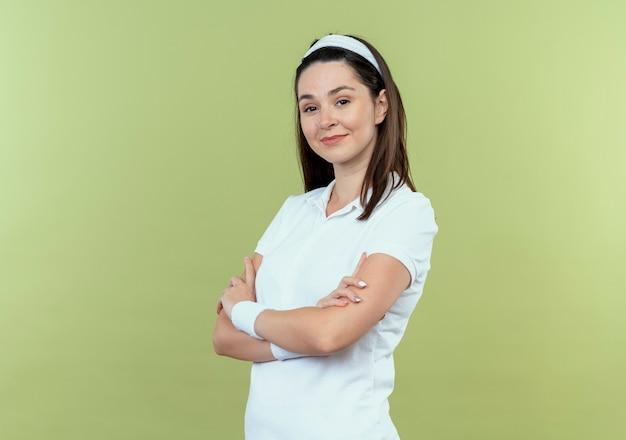 Jonge fitness vrouw in hoofdband camera kijken met zelfverzekerde uitdrukking met gekruiste armen staande over lichte achtergrond