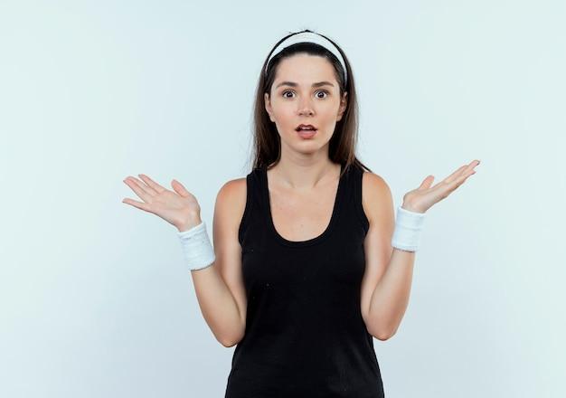 Jonge fitness vrouw in hoofdband camera kijken verward en onzeker spreidende armen aan de zijkant staande op witte achtergrond