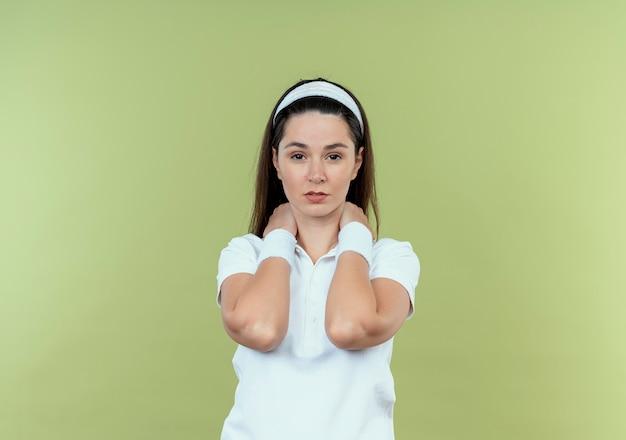 Jonge fitness vrouw in hoofdband haar nek aanraken met ernstig gezicht staande over lichte muur