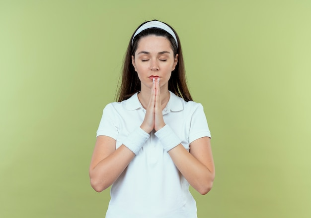 Jonge fitness vrouw in hoofdband hand in hand samen als bidden met gesloten ogen permanent over lichte achtergrond