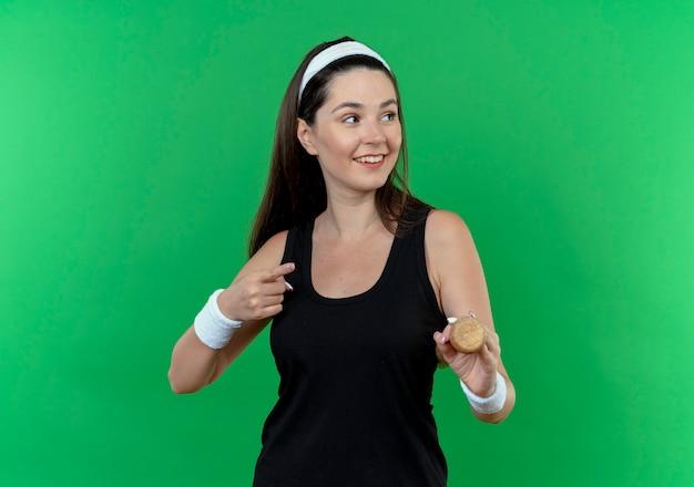 Jonge fitness vrouw in hoofdband houden honkbalknuppel opzij glimlachend met blij gezicht wijzend met vinger naar de kant staande over groene muur