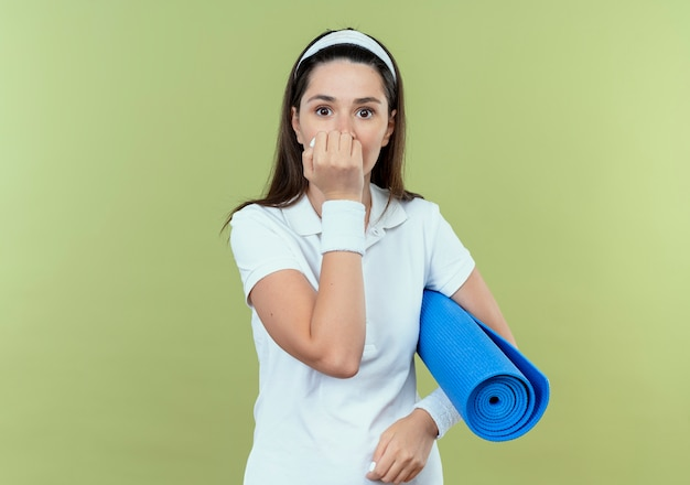 Jonge fitness vrouw in hoofdband houden yoga mat camera kijken beklemtoonde en nerveuze nagels bijten permanent over lichte achtergrond
