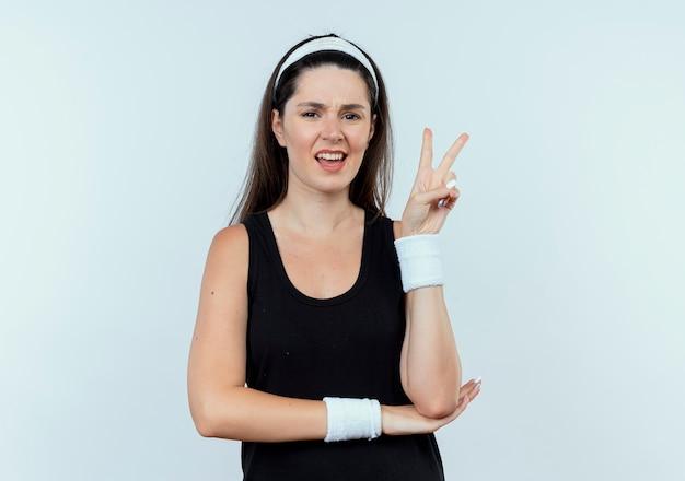 Jonge fitness vrouw in hoofdband kijken camera glimlachend weergegeven: overwinning teken staande op witte achtergrond