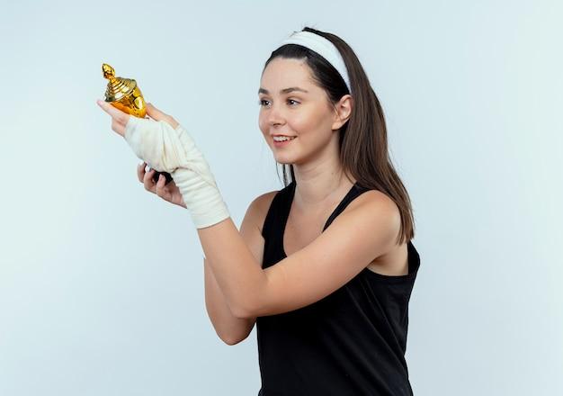 Jonge fitness vrouw in hoofdband kijken naar trofee in haar handen blij en positief staande op witte achtergrond