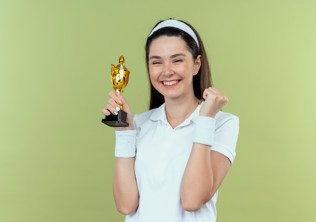 Jonge fitness vrouw in hoofdband met haar trofee blij en opgewonden gebalde vuist staande over lichte muur