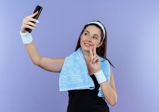 Jonge fitness vrouw in hoofdband met handdoek om de nek kijken naar het scherm van haar smartphone selfie te nemen met overwinning zingen glimlachend staande over blauwe achtergrond