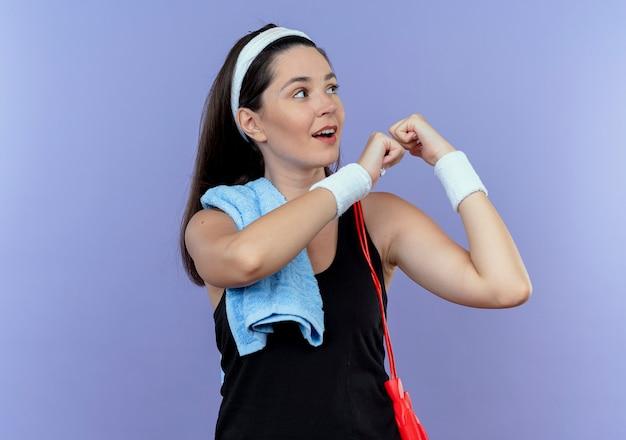 Jonge fitness vrouw in hoofdband met handdoek op haar schouder opzij kijken balde vuist met zelfverzekerde uitdrukking staande over blauwe muur