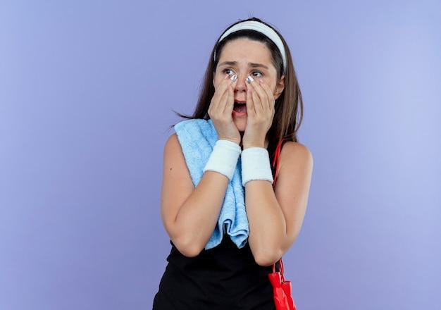 Jonge fitness vrouw in hoofdband met handdoek op haar schouder opzij kijken geschokt met wijd open mond staande over blauwe muur