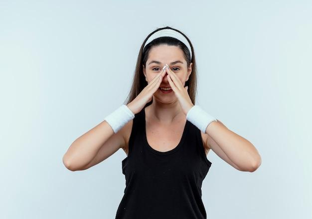 Jonge fitness vrouw in hoofdband met handen in de buurt van gezicht lacht vrolijk permanent over witte muur