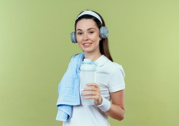Jonge fitness vrouw in hoofdband met koptelefoon en handdoek op schouder bedrijf fles water glimlachend staande over lichte muur