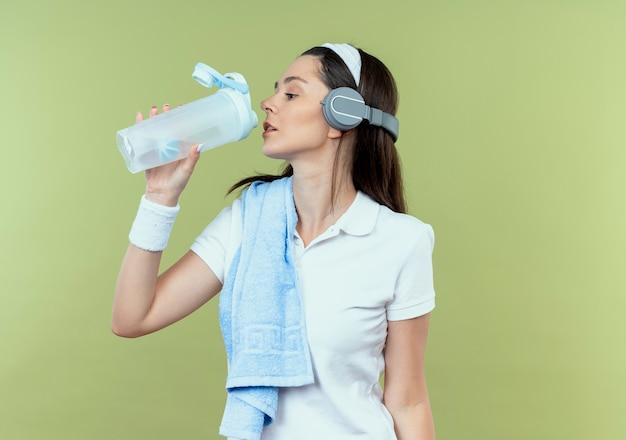 Jonge fitness vrouw in hoofdband met koptelefoon en handdoek op schouder drinkwater na training staande over lichte muur