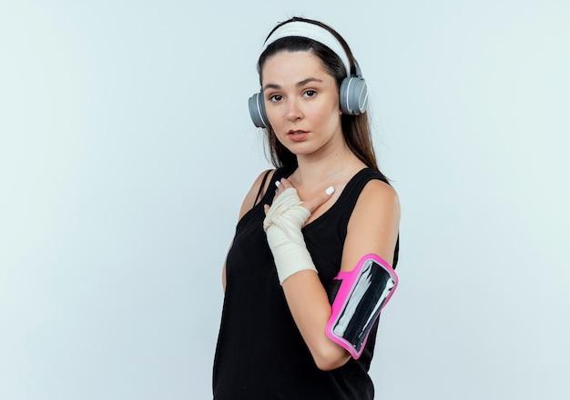 Jonge fitness vrouw in hoofdband met koptelefoon en smartphone armband met hnad op haar borst staande over witte muur