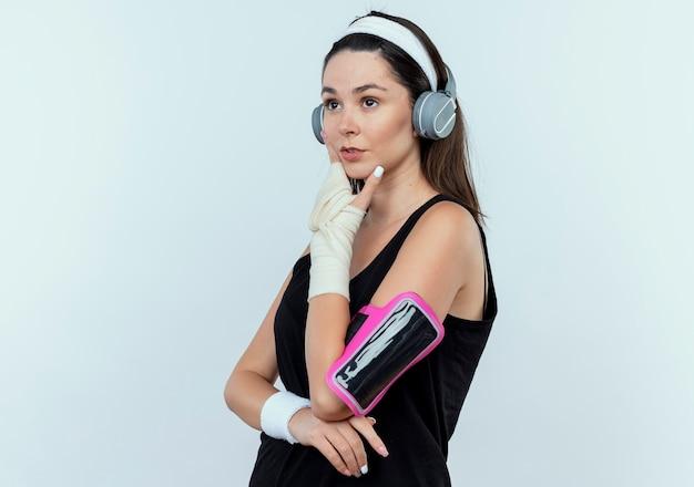 Jonge fitness vrouw in hoofdband met koptelefoon en smartphone armband opzij kijken met peinzende uitdrukking met hand op kin denken staande over witte muur