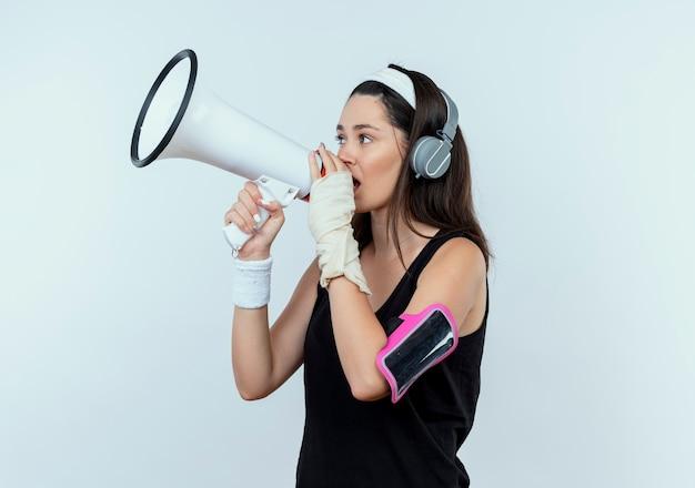 Jonge fitness vrouw in hoofdband met koptelefoon en smartphone armband schreeuwen naar megafoon staande op witte achtergrond