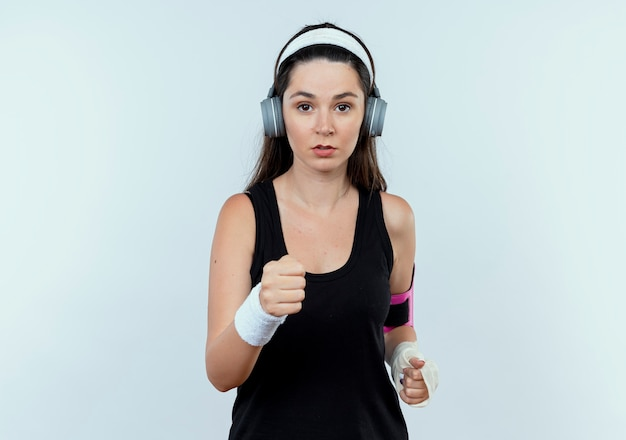Jonge fitness vrouw in hoofdband met koptelefoon en smartphone armband uit te werken camera kijken met ernstig gezicht staande op witte achtergrond