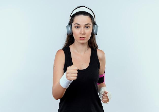 Jonge fitness vrouw in hoofdband met koptelefoon en smartphone armband uit te werken met ernstige gezicht staande over witte muur