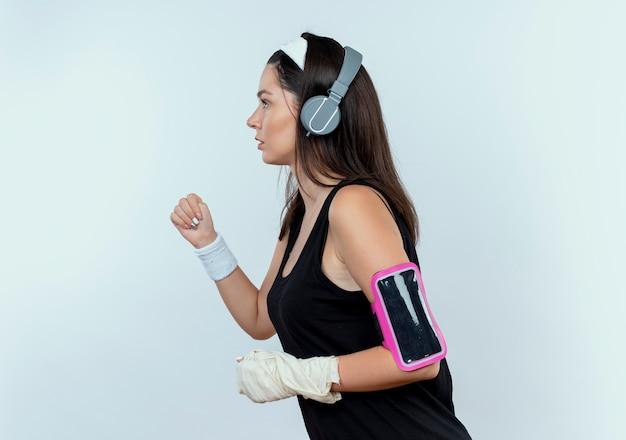 Jonge fitness vrouw in hoofdband met koptelefoon en smartphone armband uit te werken staande over witte muur