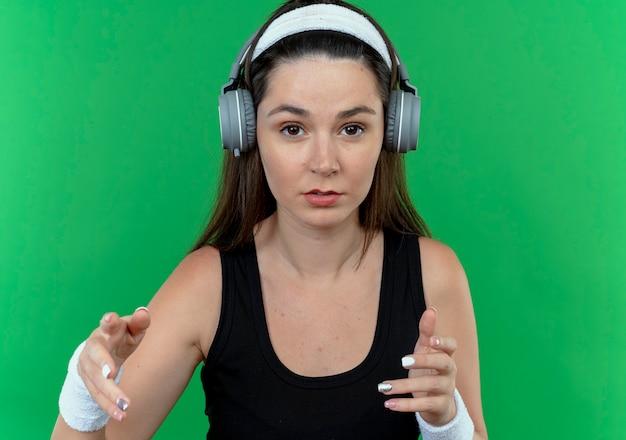 Jonge fitness vrouw in hoofdband met koptelefoon kijken camera met ernstig gezicht met armen uit staande over groene achtergrond
