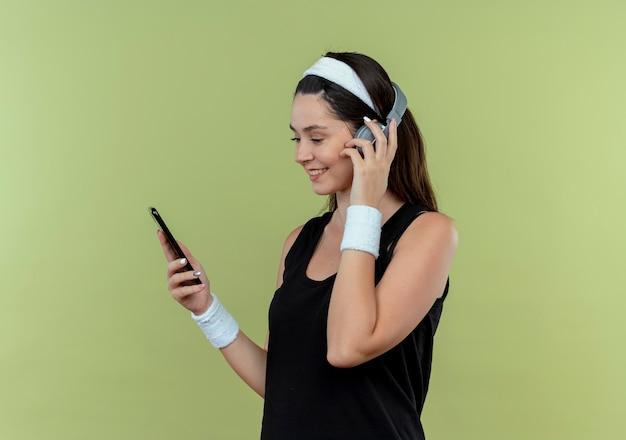 Jonge fitness vrouw in hoofdband met koptelefoon kijken naar scherm van haar smartphone zoeken muziek staande over lichte muur