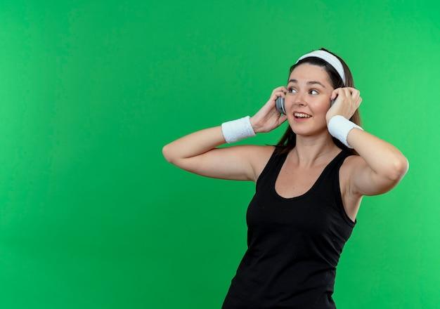 Jonge fitness vrouw in hoofdband met koptelefoon opzij kijken glimlachend genieten van haar favoriete muziek staande over groene muur
