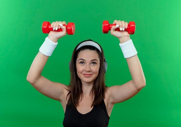 Jonge fitness vrouw in hoofdband met koptelefoon uit te werken met halters glimlachend vertrouwen staande over groene achtergrond