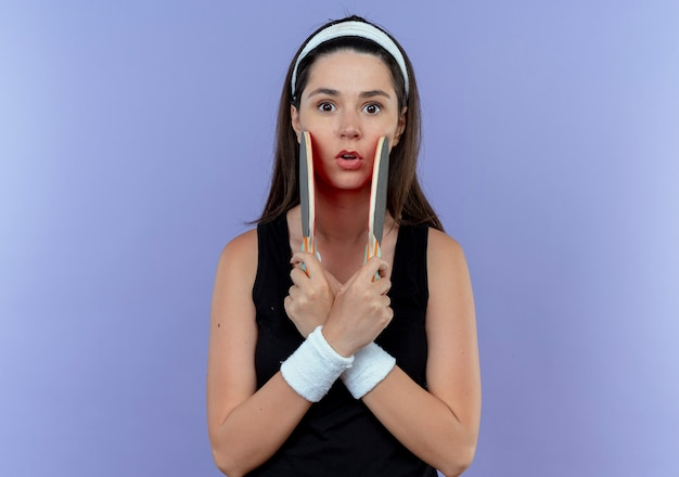 Jonge fitness vrouw in hoofdband met rackets voor tafeltennistafel verrast kruising handen permanent over blauwe muur
