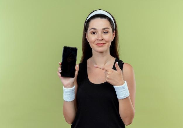 Jonge fitness vrouw in hoofdband met smartphone pointng met vinger naar het glimlachend zelfverzekerd staande over lichte muur