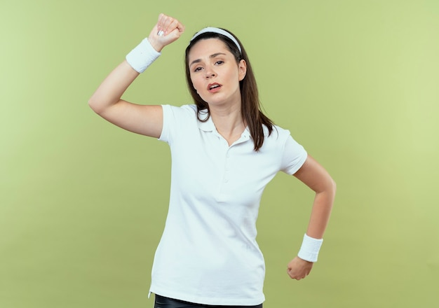 Jonge fitness vrouw in hoofdband oefeningen maken kijken moe staande over lichte muur